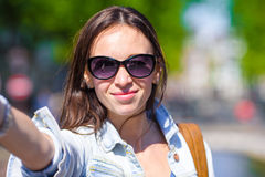 Young woman taking self portrait in european city outdoors. Young adult holding smartphone camera to take a picture of Stock Image