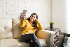 Young Woman Taking Self-Portrait At Home. Gorgeous woman posing for a selfie while sitting on sofa in living room stock photos