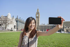 Young woman taking self portrait through smart phone against Big Ben at London, England, UK stock images