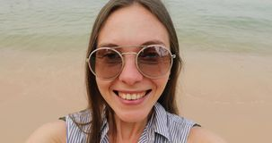 Young woman taking selfie on the beach. POV stock video footage