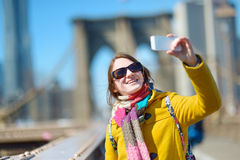 Young woman taking a selfie on Brooklyn Bridge Royalty Free Stock Photography