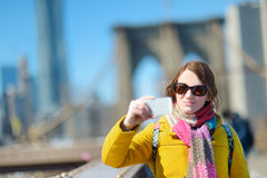 Young woman taking a selfie on Brooklyn Bridge Royalty Free Stock Image