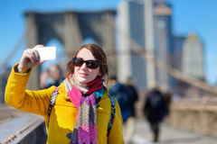Young woman taking a selfie on Brooklyn Bridge Stock Photos