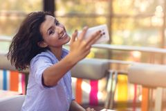 Young woman taking a selfie in coffee shop royalty free stock photography
