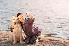 Young woman taking selfie with dog on beach. Pet care. Young woman taking selfie with her dog on beach. Pet care Royalty Free Stock Image
