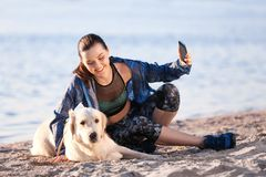Young woman taking selfie with dog on beach. Pet care. Young woman taking selfie with her dog on beach. Pet care Stock Photo