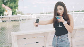 Young woman taking selfie with goblet of blue cocktail on the beach in 4K.  stock footage