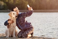 Young woman taking selfie with her dog on beach. Pet care. Young woman taking selfie with cute dog on beach. Pet care Stock Photography