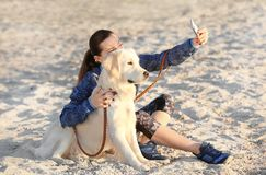 Young woman taking selfie with her dog on beach. Pet care. Young woman taking selfie with cute dog on beach. Pet care Stock Photo