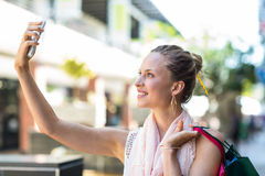 Young woman taking a selfie with her shopping bags Stock Photo