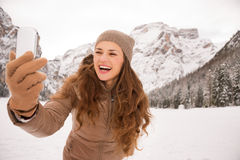 Young woman taking selfie outdoors among snow-capped mountains Royalty Free Stock Image