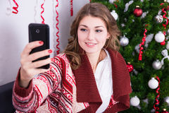 Young woman taking selfie photo with mobile phone near christmas Royalty Free Stock Image