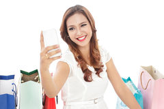 Young woman taking selfie photo with mobilephone while sitting b. Attractive young woman taking selfie photo with mobilephone while sitting between shopping bags Royalty Free Stock Photo