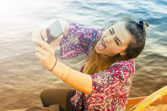 Young woman taking a selfie and pulling out her tongue. Young woman sitting by the water and taking a selfie and pulling out her tongue stock photography