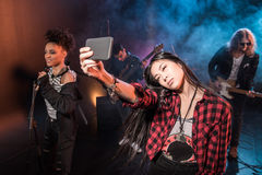 Young woman taking selfie with rock and roll band performing concert. Young women taking selfie with rock and roll band performing concert on stage Royalty Free Stock Photos