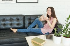 Young woman taking selfie while sitting on sofa at home stock image