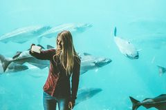 Young woman taking selfie by smartphone at big aquarium Stock Photo