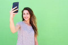 Young woman taking a selfie and smiling against green background Stock Image