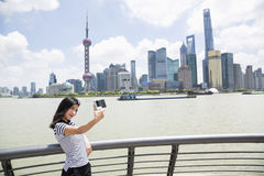Young woman taking selfie while standing by railing against Pudong skyline.  Stock Image