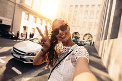 Young woman taking selfie in a street surrounded by buildings. Stock Photos