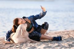 Young woman taking selfie with together her dog on beach. Pet care. Young woman taking selfie with together cute dog on beach. Pet care Stock Photo