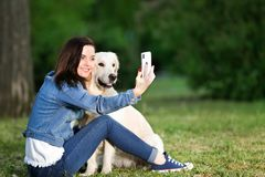 Young woman taking selfie together with her dog in park. Pet care. Young woman taking selfie together with cute dog in park. Pet care Stock Image