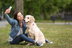 Young woman taking selfie together with her dog in park. Pet care. Young woman taking selfie together with her cute dog in park. Pet care Royalty Free Stock Photos