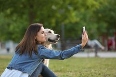 Young woman taking selfie with her dog in park. Pet care. Young woman taking selfie together with her dog in park. Pet care Royalty Free Stock Photography