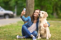Young woman taking selfie with her dog in park. Pet care. Young woman taking selfie together with her dog in park. Pet care Royalty Free Stock Photo