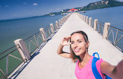 Young woman taking selfie. Travel and tourism. Young woman taking selfie on jetty Royalty Free Stock Images