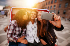 Young woman taking selfie on tricycle with friends Royalty Free Stock Photography