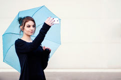 Young woman taking a selfie with umbrella. Hipster young woman taking a selfie with blue umbrella Stock Photo