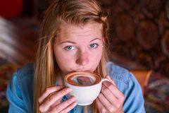 Young woman taking a sip of coffee with her face printed on. Royalty Free Stock Image