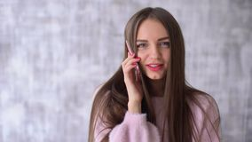 Young woman talk on the smartphone. she smiling and looking at camera over gray background. 4 k Happy girl with a white. Happy Beautiful woman in pink blouse stock video footage