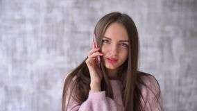 Happy Beautiful woman in pink blouse talking by the smartphone, she smiling and looking at camera over gray background. Young woman talk on the smartphone. she stock video footage