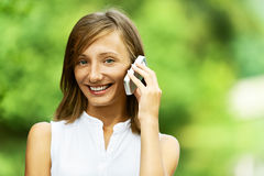 Young woman talking on cell phone. Pretty young woman talking on cell phone, against green of summer park royalty free stock images