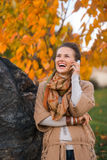 Young woman talking cell phone in autumn outdoors in evening Stock Photo