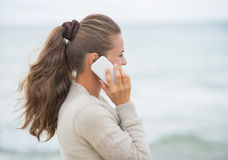 Young woman talking cell phone on cold beach Royalty Free Stock Photos