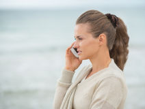 Young woman talking cell phone on cold beach Stock Photo