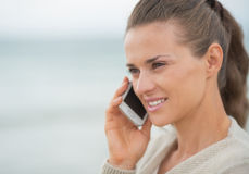 Young woman talking cell phone on cold beach Royalty Free Stock Photography