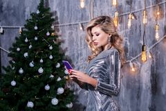Young woman talking cell phone in loft apartment. stylish woman holding phone looking at screen at christmas tree lights. seasonal royalty free stock image