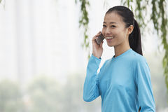 Young woman talking on cell phone in the park Stock Images