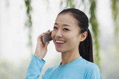 Young woman talking on cell phone in the park Royalty Free Stock Photos