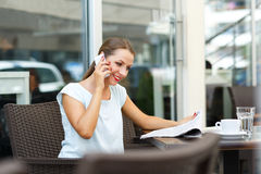 Young woman talking on the cell phone and reading a newspaper in. Attractive young woman talking on the cell phone and reading a newspaper in a coffee shop Stock Photos