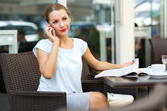 Young woman talking on the cell phone and reading a newspaper in. Attractive young woman talking on the cell phone and reading a newspaper in a coffee shop Stock Image