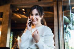 Young woman talking on cell phone while sitting alone in coffee shop.Smiling girl has telephone conversation while resting in cafe royalty free stock photography