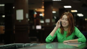 The young woman is talking on the cell phone sitting at the table in the cafe touching her loose red hair. stock footage