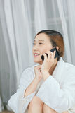 A young woman talking by cell phone in spa salon. Indoors Royalty Free Stock Photography