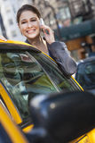 Young Woman Talking on Cell Phone By Yellow Taxi Stock Photos