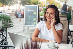 Young woman talking on cellphone at a cafe Stock Photography